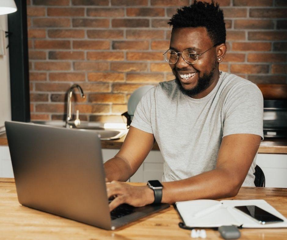 Man types on laptop